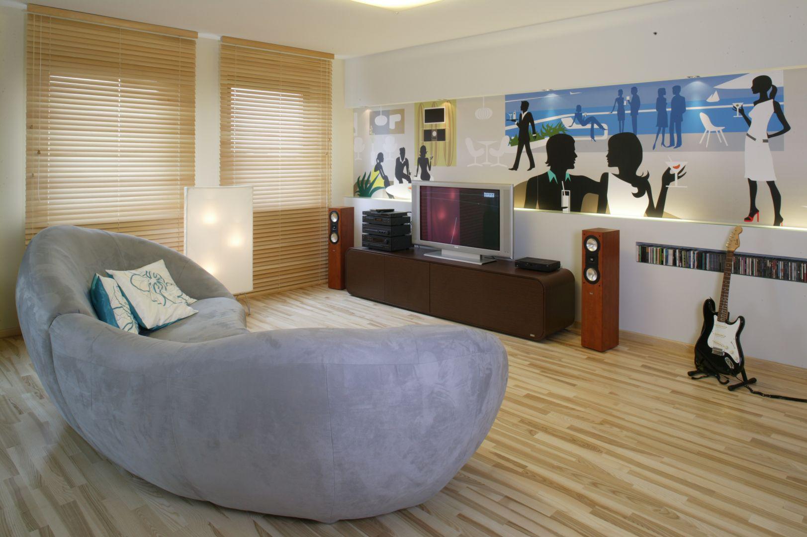 Szara sofa o opływowej formie pięknie komponuje się z oryginalną tapetą na ścianie. Projekt: Katarzyna Mikulska-Sękalska. Fot. Monika Filipiuk-Obałek