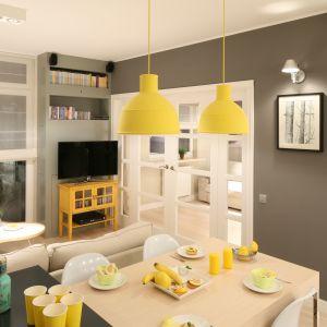 Żółty stolik RTV oraz lampy nadają styl oraz ocieplają aranżację. Projekt: Lucyna Kołodziejska. Fot. Bartosz Jarosz