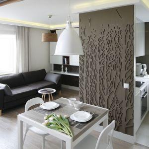 W małym mieszkaniu dobrze jest otworzyć na siebie pomieszczenia, ponieważ całe wnętrze wyda się wówczas większe. Jadalnia ulokowana w przejściu między kuchnią, a salonem to pomysłowe oraz wygodne rozwiązanie. Projekt: Małgorzata Mazur. Fot. Bartosz Jarosz