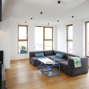 Jasny salon zaaranżowany w minimalistycznym stylu. Szara sofa w zestawieniu z stolikiem opartym na metalowym stelażu tworzy dekoracyjną kompozycję. Projekt: Monika i Adam Bronikowscy. Fot. Bartosz Jarosz