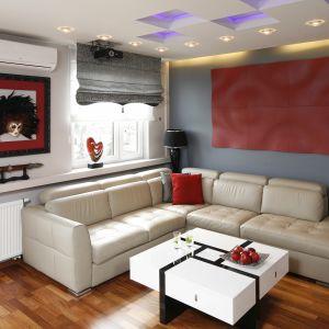 Salon zaaranżowany w nowoczesnym stylu. Dominują w nim zimne biele i szarości. Całość ociepla podłoga wykończona drewnem oraz bordowe akcenty. Projekt: Jolanta Kwilman. Fot. Bartosz Jarosz