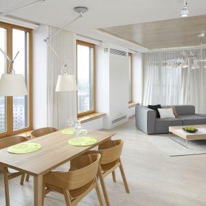 Jasny salon z jadalnią w mieszkaniu w bloku. Drewniany stół oraz krzesła pięknie ocieplają aranżację i nawiązują do stylistyki panującej w salonie. Projekt Maciej Brzostek. Fot. Bartosz Jarosz