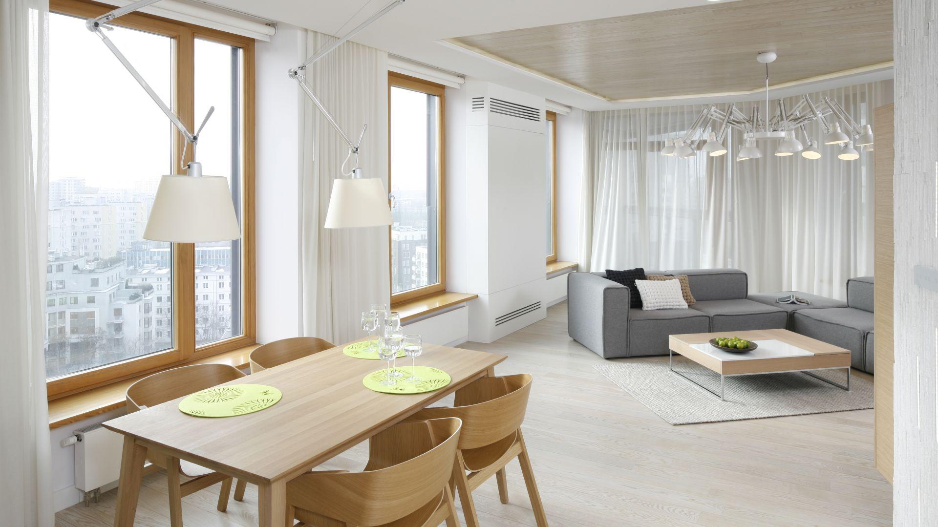 Jasny salon z jadalnią w mieszkaniu w bloku. Drewniany stół oraz krzesła pięknie ocieplają aranżację. Projekt: Maciej Brzostek. Fot. Bartosz Jarosz