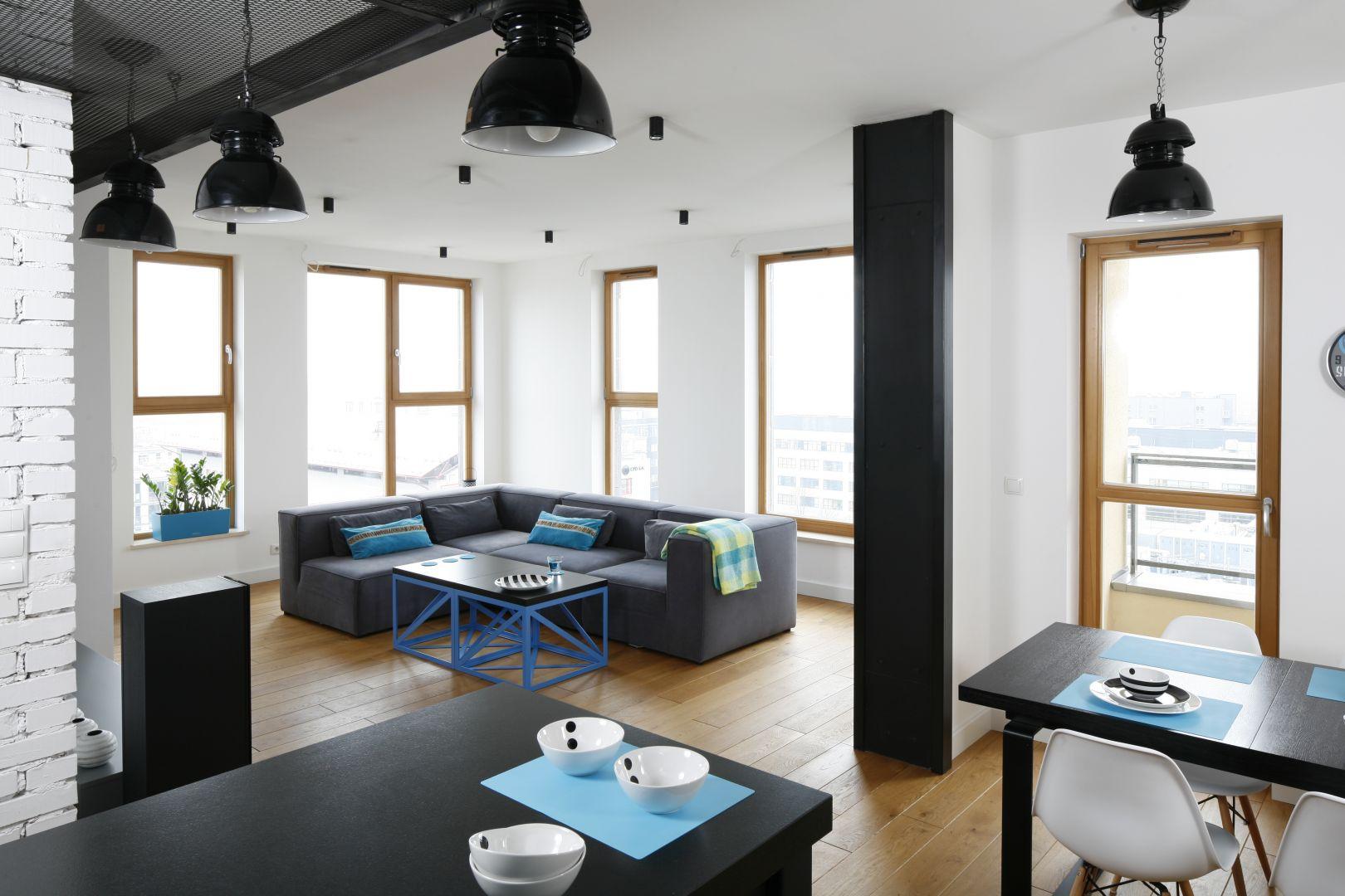 Salon z jadalnią zainspirowany stylistyką industrialną. Czarny stół połączono na zasadzie kontrastu z białymi krzesłami. Projekt: Monika i Adam Bronikowscy. Fot. Bartosz Jarosz