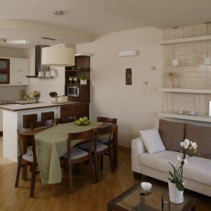 Białą kuchnię otwartą na salon ocieplono wstawkami z drewna o ciepłym odcieniu. Stół jadalniany odpowiada im kolorystycznie, dzięki czemu całość prezentuje się spójnie wizualnie. Projekt: Lucyna Stefaniak. Fot. Bartosz Jarosz