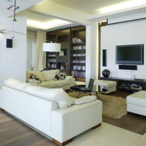 Duży salon usytuowany na dolnej kondygnacji domku jednorodzinnego. Jasne meble dodatkowo powiększają przestrzeń. Projekt: Ewelina Jankowska. Fot. Bartosz Jarosz