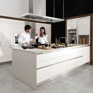 Kuchnia Cristallo. Doskonałym kontrapunktem dla zimnych, białych frontów w połysku są panele o wzorze ciepłego orzecha. Przełamują one zimną biel dodając kuchni elegancji. Fot. WFM Kuchnie