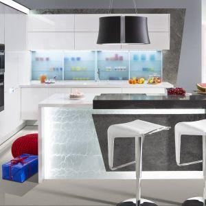 W kuchni Siena White zastosowano odważne połączenie materiałów: biały lakier na wysoki połysk z fornirem kamiennym. Naturalny, chropowaty łupek przełamuje chłodną, gładką powierzchnię frontów. Fot. Kuchnie Halupczok