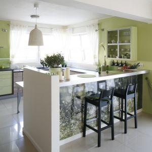Kuchnia utrzymana w jasno zielonej tonacji prezentuje się bardzo subtelnie i uroczo. Niebanalnym elementem wnętrza jest półwysep wykończony panelem dekoracyjnym. Projekt: Marta Kruk. Fot. Bartosz Jarosz