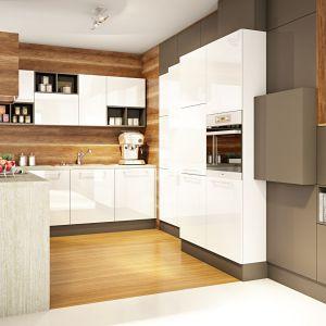 Biała kuchnia na wysoki połysk jest bardzo modna i wyrazista. Można ją ocieplić drewnem, którym wyłożymy ściany nad blatem. Fot. Kuchnie Moelke