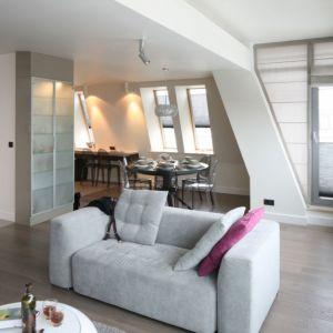 Niewielka sofa akcentuje podział wnętrza na strefy. Projekt Małgorzata Borzyszkowska. Fot. Bartosz Jarosz