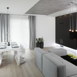 Biały stół ze stylowymi krzesłami na tle ciemnej ściany prezentuje się bardzo elegancko. Całość idealnie dopełnia duża sofa. Projekt Karolina Stanek-Szadujko, Łukasz Szadujko. Fot. Bartosz Jarosz