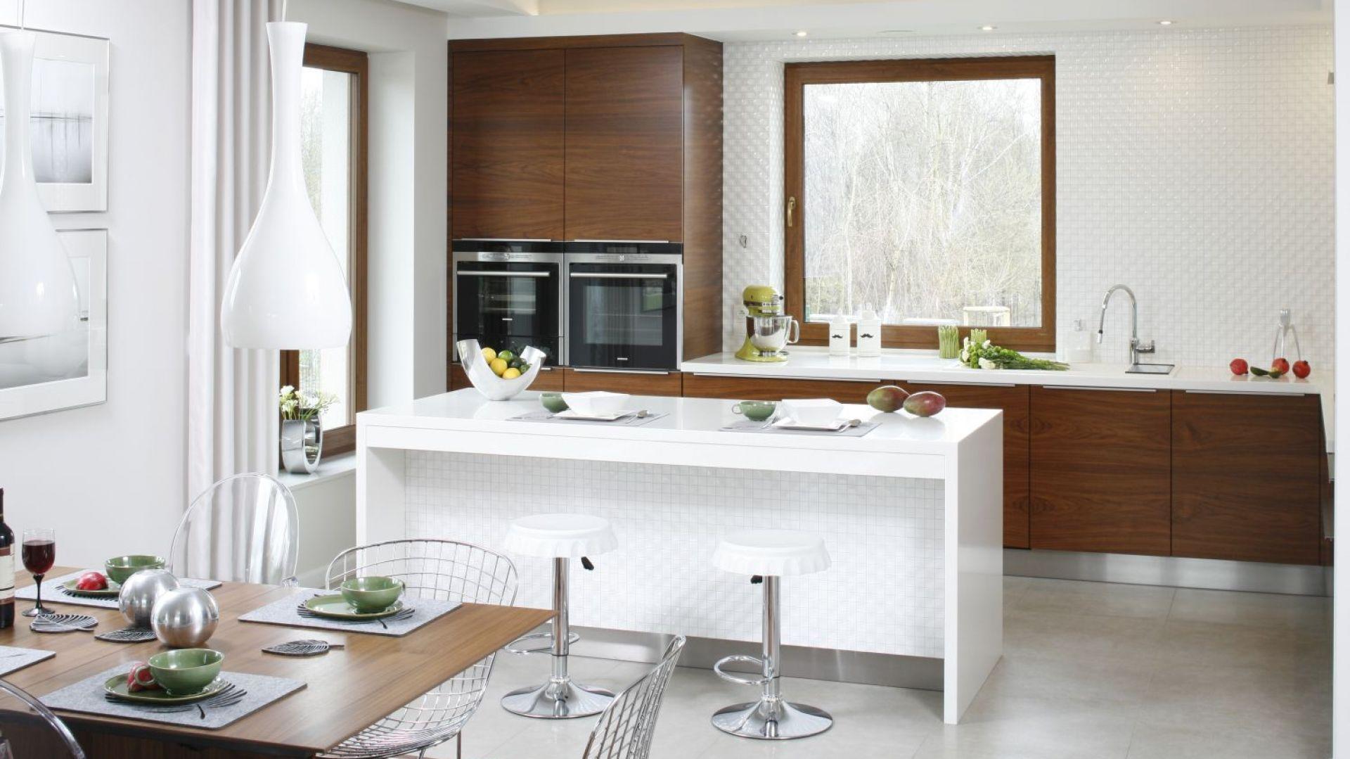Biel i drewno doskonale się ze sobą łączą. W tej aranżacji biała wyspa rozjaśnia kuchenne wnętrze i jednocześnie sprawia, że stało się one bardziej funkcjonalne. Projekt: Piotr Stanisz. Fot. Bartosz Jarosz
