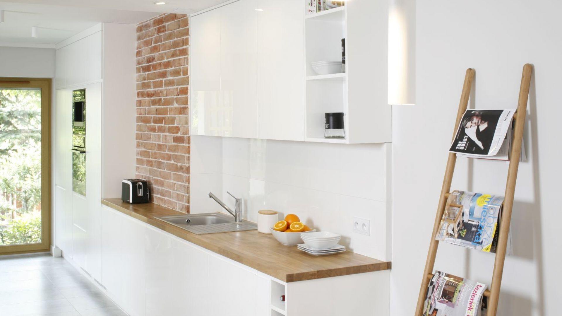 Białe kuchnie warto przełamać ciekawymi detalami. W tym wnętrzu jest to element ściany wykończony surową, czerwoną cegłą. Projekt: Agata Piltz. Fot. Bartosz Jarosz