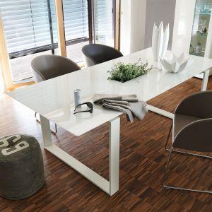 Stół Neo Vision – szklany blat w kolorze białym wsparty na białych płozach z lakierowanego mdf-u. Fot.  Hülsta