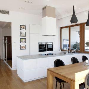 Biała kuchnia w nowoczesnym stylu. Wyspa ze strefą gotowania pozwala przygotowywać posiłek twarzą do gości. Fot. Studio Prostych Form