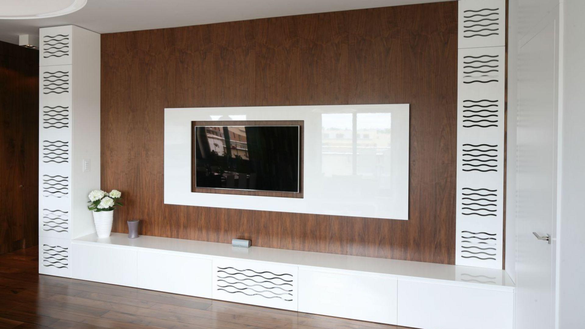 Ściana telewizyjna oparta na kontraście zimnej bieli na wysoki połysk oraz ciepłego drewna. Projekt Agnieszka Ludwinowska. Fot. Bartosz Jarosz