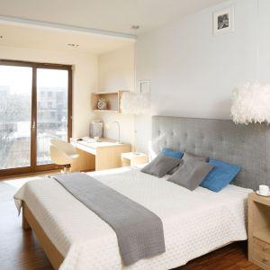 Drewniane łóżko z szarym zagłówkiem prezentuje się bardzo przytulnie. Można je ożywić kolorowymi dodatkami. Projekt: Marta Kruk. Fot. Bartosz Jarosz