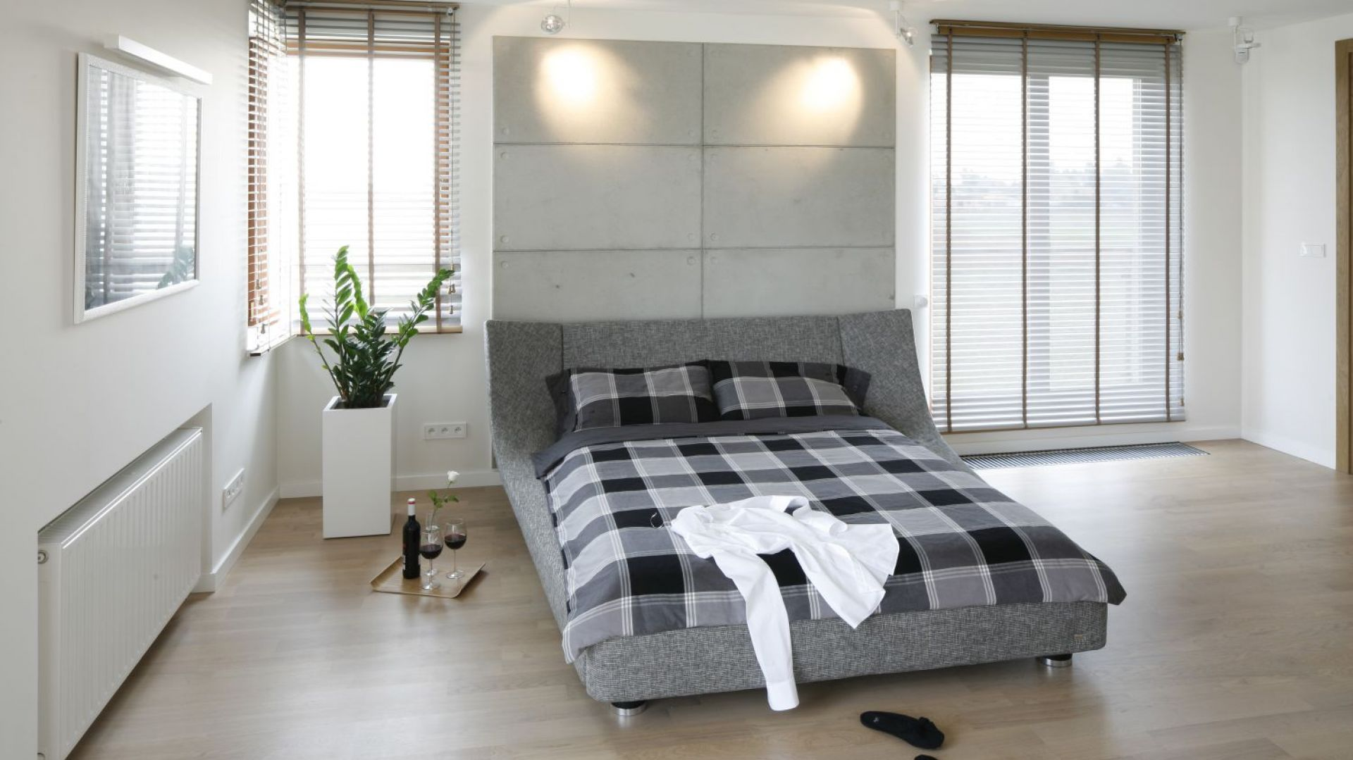Tapicerowane łóżko w szarym kolorze to nowoczesny i niezwykle modny element wnętrza. Doskonale prezentuje się na tle białej ściany. Projekt Agnieszka Ludwinowska. Fot. Bartosz Jarosz