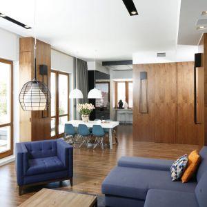 Niebieskie krzesła nawiązują do kolorystyki panującej w salonie. Dzięki temu połączeniu salon i jadalnią są estetycznie spójne. Projekt Monika i Adam Bronikowscy. Fot. Bartosz Jarosz