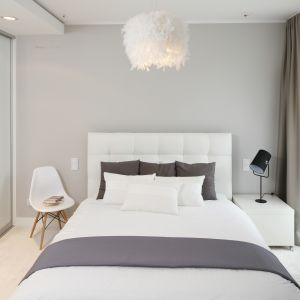 Elegancka sypialnia utrzymana w jasnej tonacji. Białe łóżko z pikowanym zagłówkiem idealnie pasuje do tej aranżacji. Projekt: Małgorzata Galewska. Fot. Bartosz Jarosz