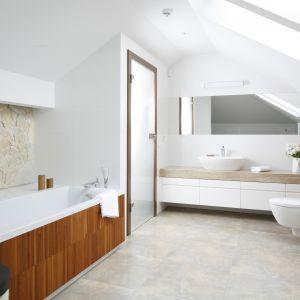 Biała szafka na całą długość ściany sprawia, że łazienka wygląda na nieco większą. Drewniany blat z grubej deski czyni j bardziej naturalną i przytulną. Projekt: Piotr Stanisz. Fot. Bartosz Jarosz