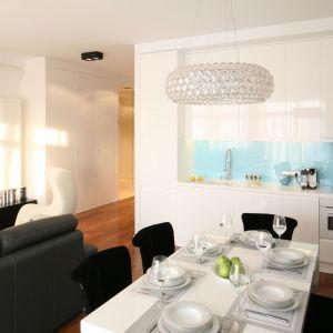 Maleńki aneks otwarty na salon będzie wydawał się większy, jeśli wybierzemy meble w bieli i połysku. Projekt: Anna Maria Sokołowska. Fot. Bartosz Jarosz