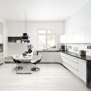 Biała, nieco surowa kuchnia oryginalnie wygląda w połączeniu z blatem z rysunkiem kamienia. Na zdjęciu kuchnia Soft Lack. Fot. Nolte