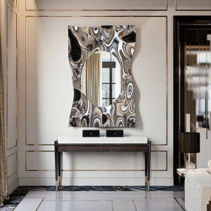 Lustro Impact Specchio z ramą przypominającą zmąconą taflę wody wykonaną z błyszczącej stali. Fot. Galeria Mebli Heban