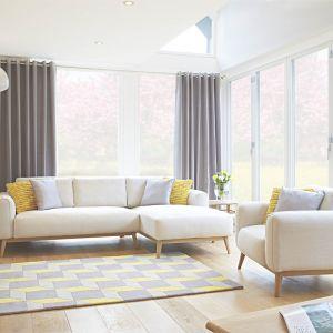 Biała sofa na cienkich nóżkach będzie prezentować się w salonie lekko i świeżo. To dobre rozwiązanie, jeśli chcemy optycznie powiększyć salon. Fot. Housing Units