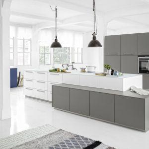 Kuchnia Soft Lack sprawdzi się we wnętrzu w stylu Loft. Posiada szklany blat oraz lakierowane fronty utrzymane w chłodnych odcieniach bieli, szarości oraz koloru niebieskiego. Fot. Nolte Küchen