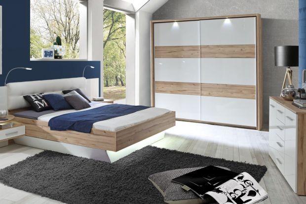 Nowoczesna sypialnia w bieli ocieplona jasnym drewnem.