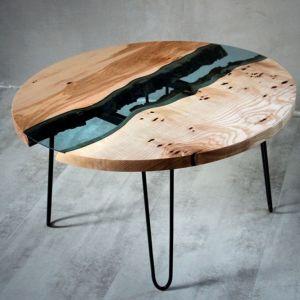 Stolik kawowy, którego blat przedzielony został błękitnym szkłem, prezentuje się nietypowo. Fot. Malita Just Wood