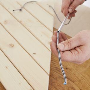 W ostatnim kroku przymocuj stolik do balustrady balkonowej. W tym celu wywierć wkrętarką IXO z adapterem do wiercenia po  3 otwory w narożniku obu blatów. Otwory powinny pasować do grubości nylonowej linki (maks. średnica 5 mm). Następnie utnij 3 równe kawałki linki. Przeprowadź linkę przez otwory, załóż elementy dystansowe pomiędzy obydwoma blatami i zawiąż supełki, zarówno pod dolnym, jak i nad górnym blatem. Zamocuj 3 górne końce linki za pomocą kółek ustalających do balustrady. Fot. Bosch