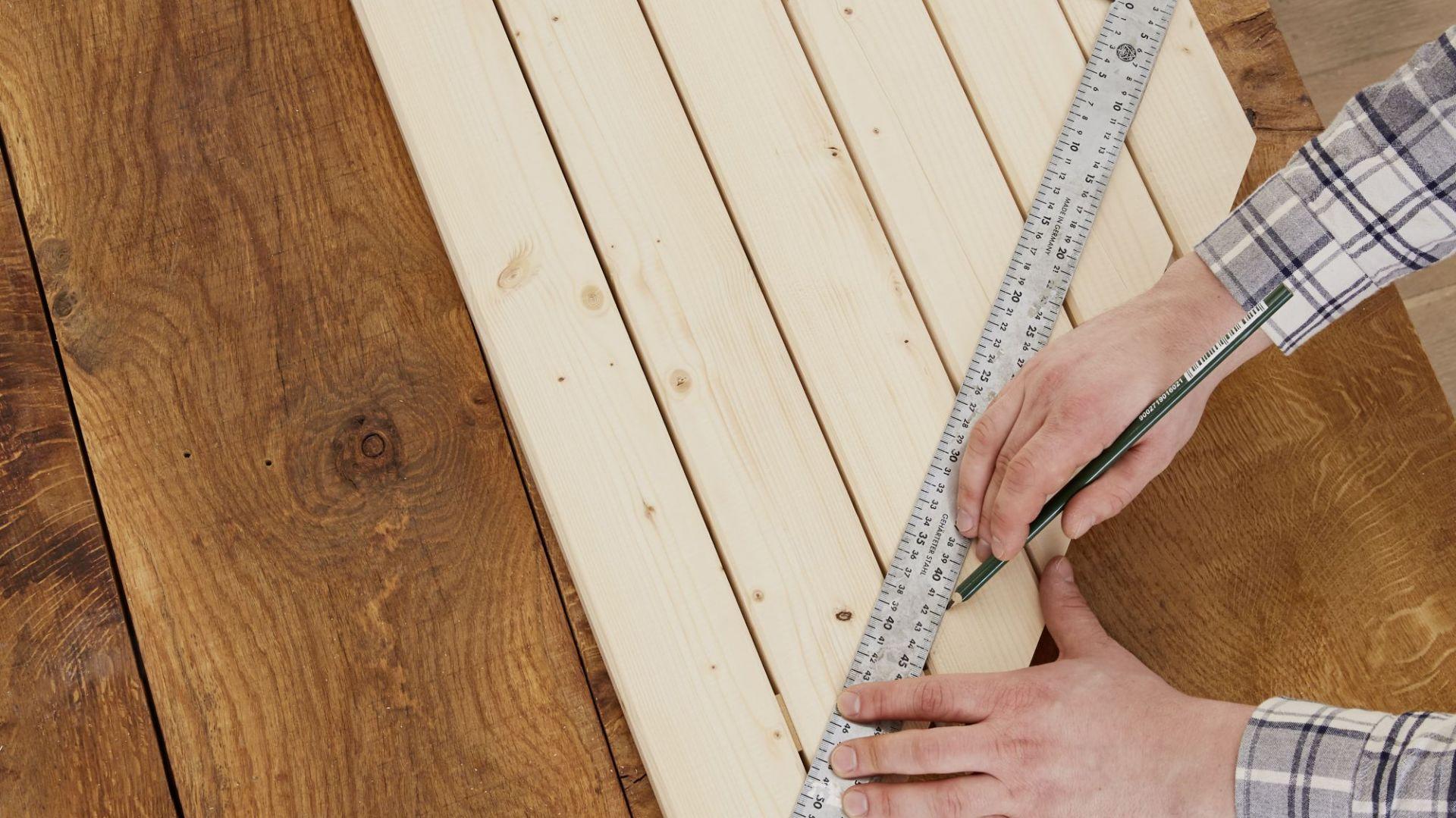 Aby stolik miał prawidłowe wymiary i dokładnie pasował do wybranego miejsca, najpierw ustal jego wymiary. W naszym przykładzie to 90 x 66 x 66 cm i wysokość ok. 30 cm. Jedną z desek potnij na 6 coraz mniejszych kawałków (90 cm, 80 cm, 60 cm, 40 cm, 20 cm i 10 cm) i ułóż je tak, aby przypominały trójkąt. Następnie, przy pomocy linijki kątowej zaznacz ołówkiem dokładne wymiary narożnika balkonu tak, aby powstał trójkąt prostokątny o dwóch ramionach takiej samej długości. Fot. Bosch