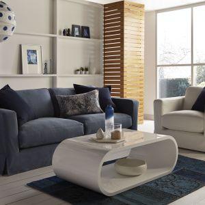 Biały stolik o obłych kształtach będzie prezentował się nowocześnie. Pod blatem jest dużo miejsca na gazety lub książki. Fot. DFS Furniture