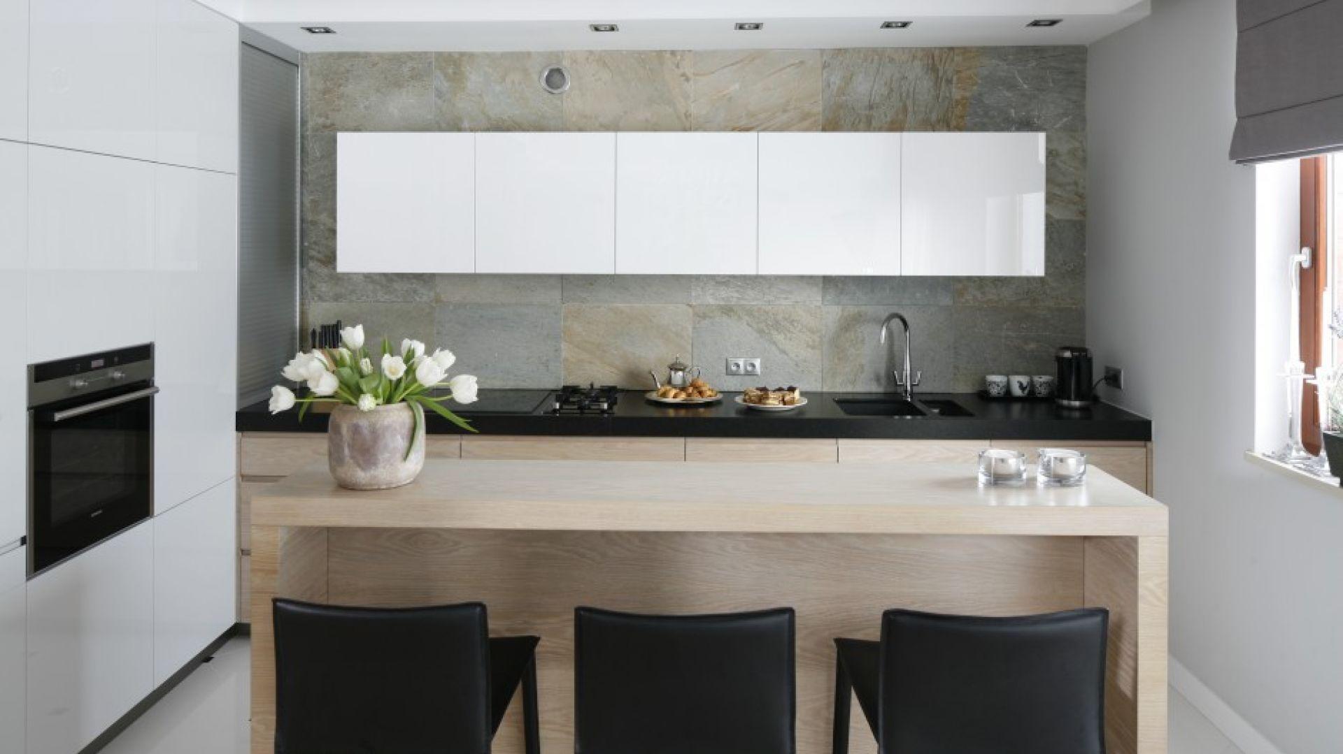 Kamienna ściana jest dekoracją całej kuchni. Od salonu oddziela ją wyspa, która pełni również rolę śniadaniowego baru. Projekt: Magdalena Smyk. Fot. Bartosz Jarosz