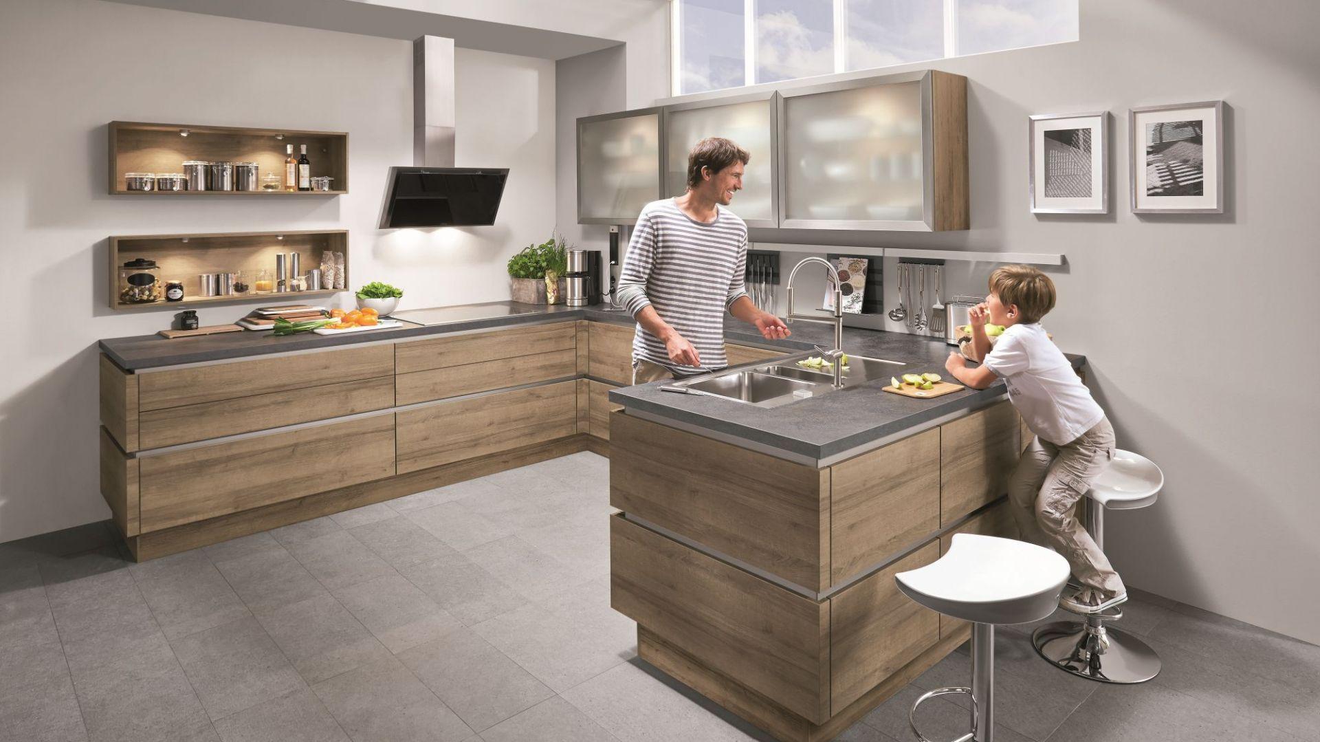 Kuchnia Riva to połączenie drewna i szarości. Transparentne górne fronty nadają aranżacji lekkości. Fot. Nobilia