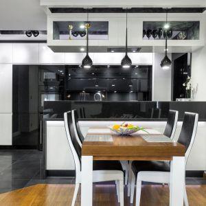 Biało-czarna kuchnia w nowoczesnym stylu. Przeszklone szafki umieszczono tuż pod sufitem. Fot. Studio AK/Max Kuchnie