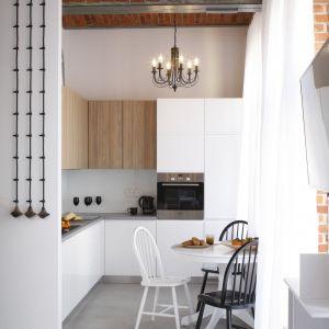 Mała kuchnia w bieli z dodatkiem drewna. Projekt Tomasz Jasiński. Fot. Bartosz Jarosz