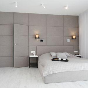 Szare łóżko na tle szarej ściany prezentuje się minimalistycznie. Projekt: Ewelina Pik, Maria Biegańska. Fot. Bartosz Jarosz