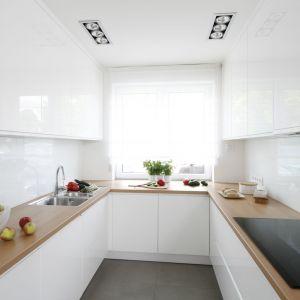 Białą kuchnię w połysku można łatwo ocieplić dzięki drewnianym blatom. Projekt: Joanna Ochota. Fot. Bartosz Jarosz