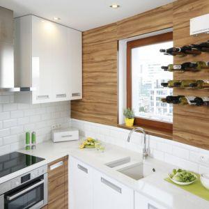 Połączenie bieli z drewnem pasuje do niewielkiej kuchni. Projekt Marta Kramkowska. Fot. Bartosz Jarosz