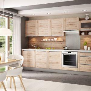 Aranżacja kuchni z drewnem nad blatem ociepli wnętrze, nada mu przytulności i ponadczasowego piękna. Fot. Kam