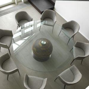 Stół z okrągłym szklanym blatem, jego podstawą jest kamienna kula. Fot. Porada