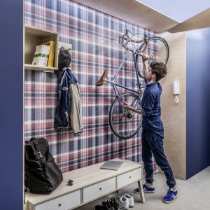 Ściana w szkocką kratę ożywi wnętrze przedpokoju, a praktyczne wieszaki pozwolą uporządkować wnętrze. Fot. Vox
