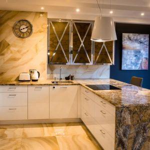 Mieszkanie zaprojektowane przez Viva Design W prostej, białej zabudowie kuchennej wykonanej przez stolarza pojawiły się szafki z dekoracyjnym fornirem zdobionym chromowanymi listwami.