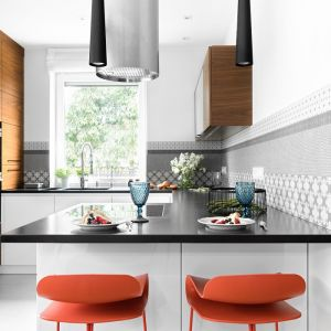 Projekt wnętrza: MM Architekci. W tej kuchni uwagę zwraca ciekawe połączenie kolorów - wysoka zabudowa z drewna, ciemny blat i biel szafek są tłem dla koralowych hokerów.