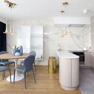 Projekt wnętrza: Kaza. Kobiecy charakter wnętrza został podkreślony między innymi przez zaokrąglone kształty mebli np. stołu i wyspy kuchennej.