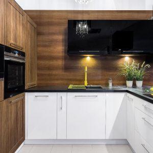 Czarny blat dobrze komponuje się z bielą frontów i drewnem reszty zabudowy. Fot. Studio Mebel Styl/Max Kuchnie